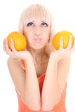 Young attractive woman with two oranges Royalty Free Stock Images