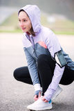 Young attractive woman tying shoelaces before a running session Royalty Free Stock Photos