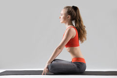 Young attractive woman in Upward Abdominal Lock pose, grey studi Royalty Free Stock Photo