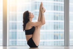 Young attractive woman in urdhva mukha paschimottanasana pose ag Stock Image