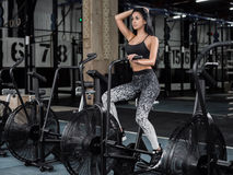 Young, attractive woman using exercise bike at the gym. Fitness Stock Photo