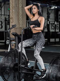 Young, attractive woman using exercise bike at the gym. Fitness Stock Photography