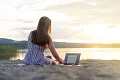 Young attractive woman using laptop on beach at sunset. Active lifestyle. Student doing homework or entrepreneur working late. Freelancer mobile office. Modern Royalty Free Stock Photo