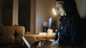 Young pretty woman using laptop computer and surfing social media sitting on coach at home in night time Stock Image