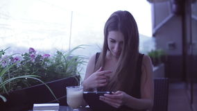 Young attractive woman using laptop while sitting in cafe. Young attractive woman using laptop while sitting in street cafe stock footage