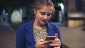 Young attractive woman using smart phone at night in city. Beautiful girl texting on smartphone outdoors. Tourist Girl. With cellphone, Night Street lights stock footage