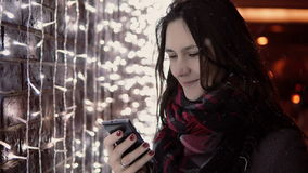 Young attractive woman using smartphone in the falling snow at Christmas night standing near lights wall, Stock Photo