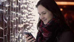 Young attractive woman using smartphone in the falling snow at Christmas night standing near lights wall, stock footage