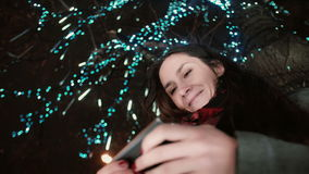 Young attractive woman using smartphone at snowy Christmas night standing under a tree decorated with sparkling lights Royalty Free Stock Images