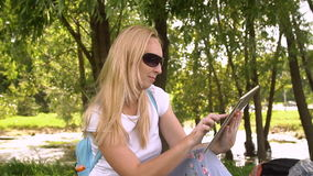 Young attractive woman using tablet, slow motion. Young attractive woman using tablet computer outdoors green grass sunny day stock video