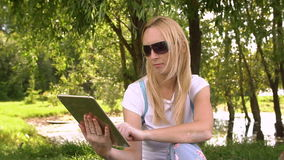 Young attractive woman using tablet, slow motion. Young attractive woman using tablet computer outdoors green grass sunny day stock footage