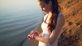 Young attractive woman using touchscreen smart watches. Female is on the sand beach near the sea outdoor stock footage