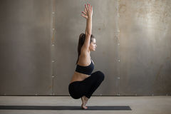 Young attractive woman in Utkatasana pose, grey studio backgroun. Young attractive woman practicing yoga, siting in Utkatasana exercise, Squat, Chair pose Stock Image