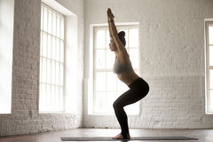 Young attractive woman in Utkatasana pose, white loft studio bac. Young attractive yogi woman practicing yoga concept, standing in Utkatasana exercise, Chair Stock Photography