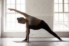 Young attractive woman in Utthita parsvakonasana pose, white lof. Young attractive yogi woman practicing yoga concept, standing in Utthita parsvakonasana Stock Images