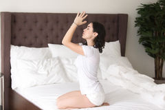 Young attractive woman in vajrasana pose on the hotel bed. Young sporty attractive woman practicing yoga at home after waking up, sitting in seiza pose Royalty Free Stock Photography