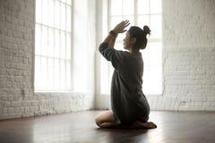 Young attractive woman in vajrasana pose, white loft studio back. Young attractive yogi woman practicing yoga concept, sitting in vajrasana exercise, seiza pose stock photo