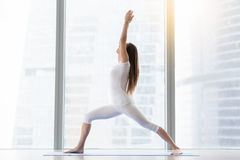 Young attractive woman in Virabhadrasana I pose against floor wi Stock Photos