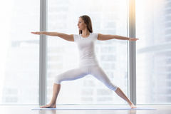 Young attractive woman in Virabhadrasana II pose against floor w royalty free stock images
