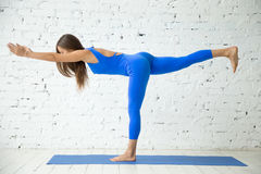 Young attractive woman in Virabhadrasana III pose, white studio Royalty Free Stock Image
