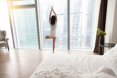 Young attractive woman in Vrksasana pose near the unmade bed Stock Photo