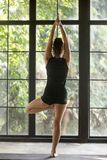 Young attractive woman in Vrksasana pose, window background. Young attractive woman practicing yoga at home, standing in Vrksasana exercise, Tree pose, working Stock Images