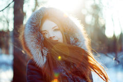 Young and attractive woman on walk, winter, warm coat with a hood Royalty Free Stock Image