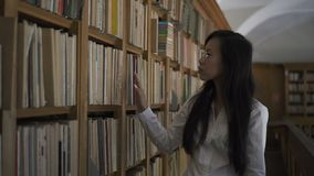 Young attractive woman is walking along university library indoors. Young attractive woman is walking along university library indoors, Asian female student stock footage