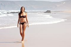 Young  attractive woman walking on the beach Stock Photography