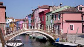 Young attractive woman walking on a bridge surrounded by colorful buildings meanwhile the boats float in the canal.