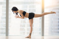 Young attractive woman in Warrior III pose against floor window Stock Photography