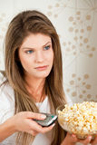 Young attractive woman wathcing TV and holding pop Royalty Free Stock Image