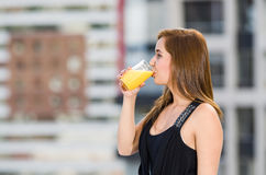 Young attractive woman wearing black dress standing on rooftop, holding glass drinking yellow drink, seen from profile. Angle, city buildings background Stock Photo