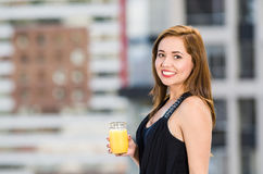 Young attractive woman wearing black dress standing on rooftop, holding glass with yellow drink, smiling to camera, city. Buildings background Stock Image