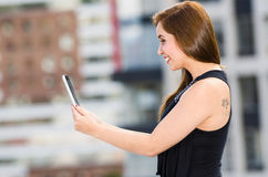 Young attractive woman wearing black dress standing on rooftop, holding tablet, seen from profile angle, city buildings. Background Royalty Free Stock Image