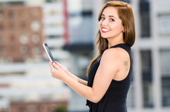 Young attractive woman wearing black dress standing on rooftop, holding tablet, smiling to camera, city buildings. Background Stock Image