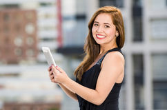 Young attractive woman wearing black dress standing on rooftop, holding tablet, smiling to camera, city buildings. Background Royalty Free Stock Image