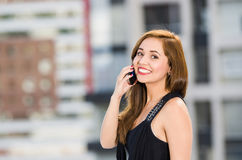 Young attractive woman wearing black dress standing on rooftop, smiling and holding mobile phone talking, city buildings. Background Stock Photos