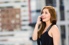 Young attractive woman wearing black dress standing on rooftop, smiling and holding mobile phone talking, city buildings. Background Stock Photo