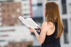 Young attractive woman wearing black dress standing on rooftop, tattoo visible left shoulder, holding book reading, seen. From behind angle, city buildings Royalty Free Stock Images