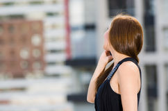 Young attractive woman wearing black dress standing on rooftop, turning away and holding mobile phone talking, city. Buildings background Royalty Free Stock Images