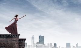 Blind woman in long red dress at top of building. Mixed media. Young attractive woman wearing blindfold and stretching hand against cityscape background royalty free stock image