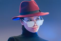 Young attractive woman wearing burgundy wide-brimmed hat looking over sunglasses covered. In frost royalty free stock photo