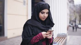 Young attractive woman wearing hijab standing in the street, typing a message on her mobile phone. Slowmotion shot.  stock footage