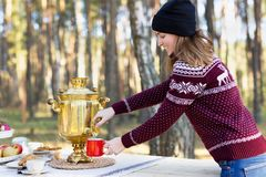 Young woman wearing jersey with hat pouring some tea using vintage russian teapot samovar. Young attractive woman wearing jersey with hat pouring some tea using stock photos