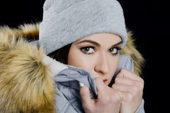 Young attractive woman wearng woollen hat and fur jacket. Isolated on black background Royalty Free Stock Image