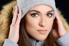 Young attractive woman wearng woollen hat and fur jacket. Isolated on black backgroubd Stock Image