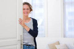 Young attractive woman welcoming you in his house Royalty Free Stock Photo