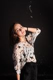 Young attractive woman in wet dress. Portrait of young attractive wet lady at black background Stock Photo