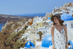 A young and attractive woman in a white dress and black hat, walking at the city of Oia, island of Santorini, Greece. Concept - of Royalty Free Stock Photo